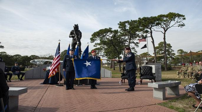 A Special Tactics pararescueman with the 24th Special Operations Wing unfurls the brigadier general flag of U.S. Air Force Brig. Gen. Claude K. Tudor, Jr., during a ceremony at Hurlburt Field, Florida, Feb. 8, 2019.
